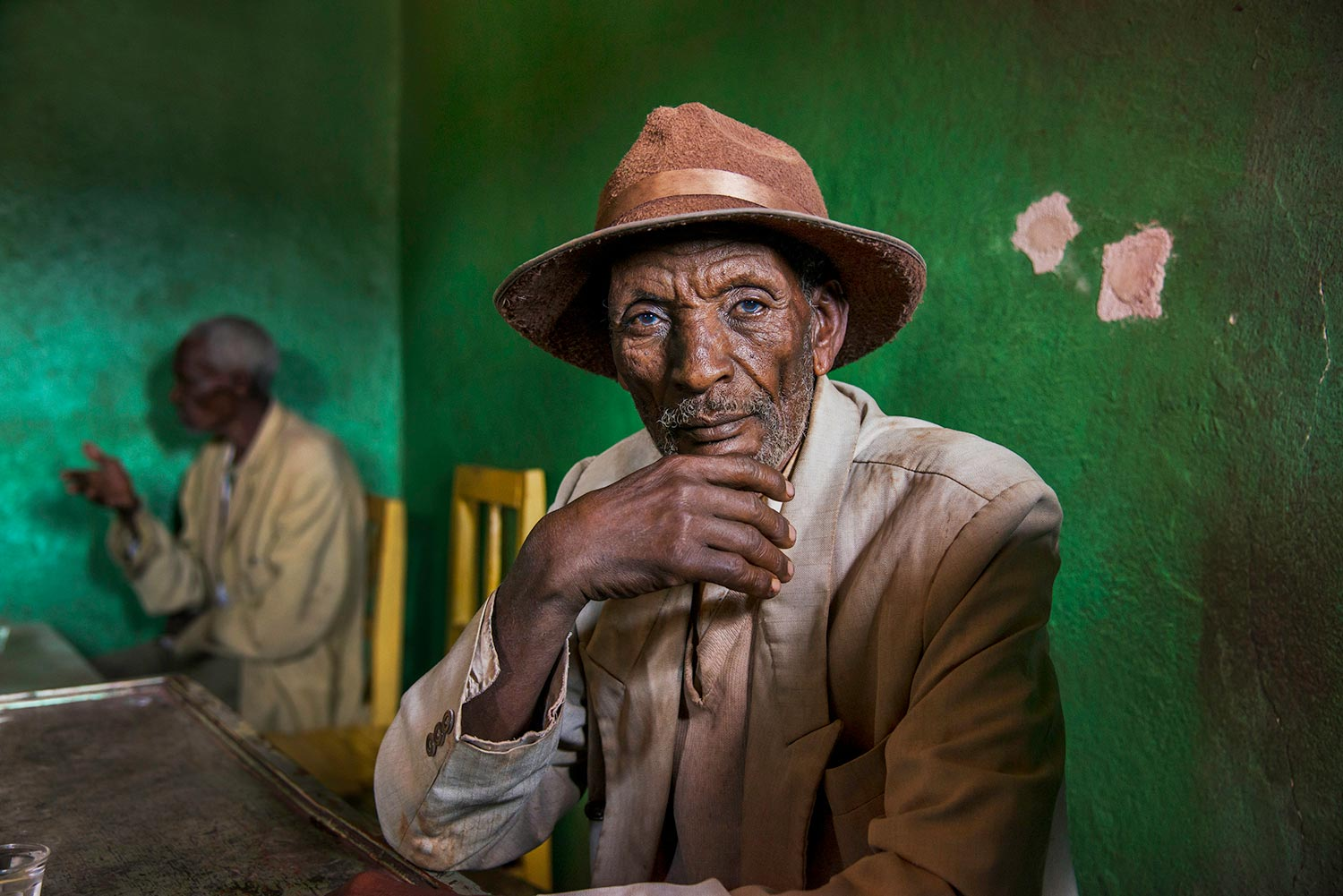 Portrait of an elderly man sitting in a green room, Ethiopia, 2014