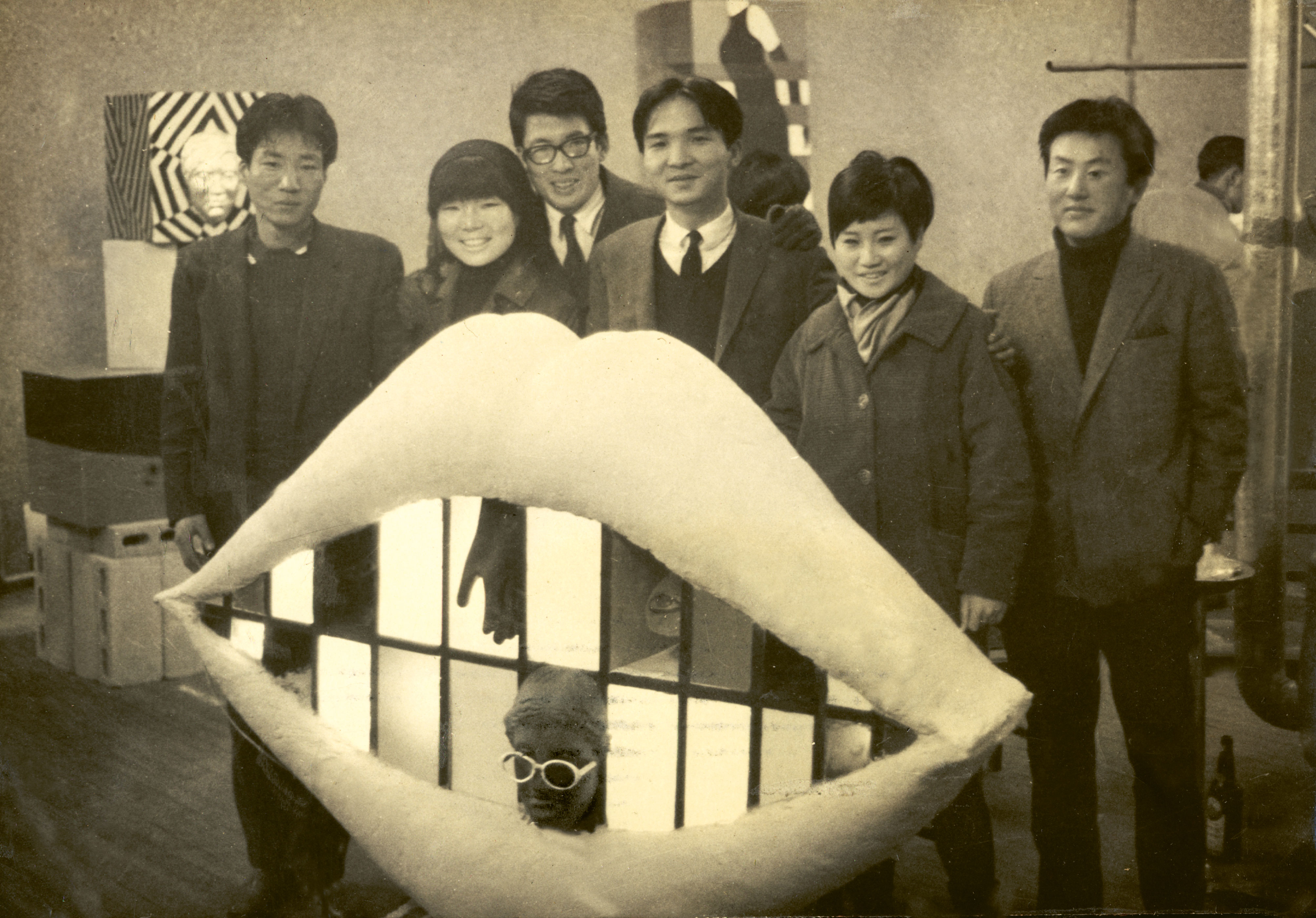 Artists of the Shinjeon Group – Kang Kuk-jin, Jung Kang-ja, Chung Chan-seung, Kim In-hwan, Shim Sun-hee, Yang Duk-soo – standing by Jung's work Kiss me (1967), at the 'Union Exhibition of Korean Young Artists', Korea Information Center, Seoul, 1967