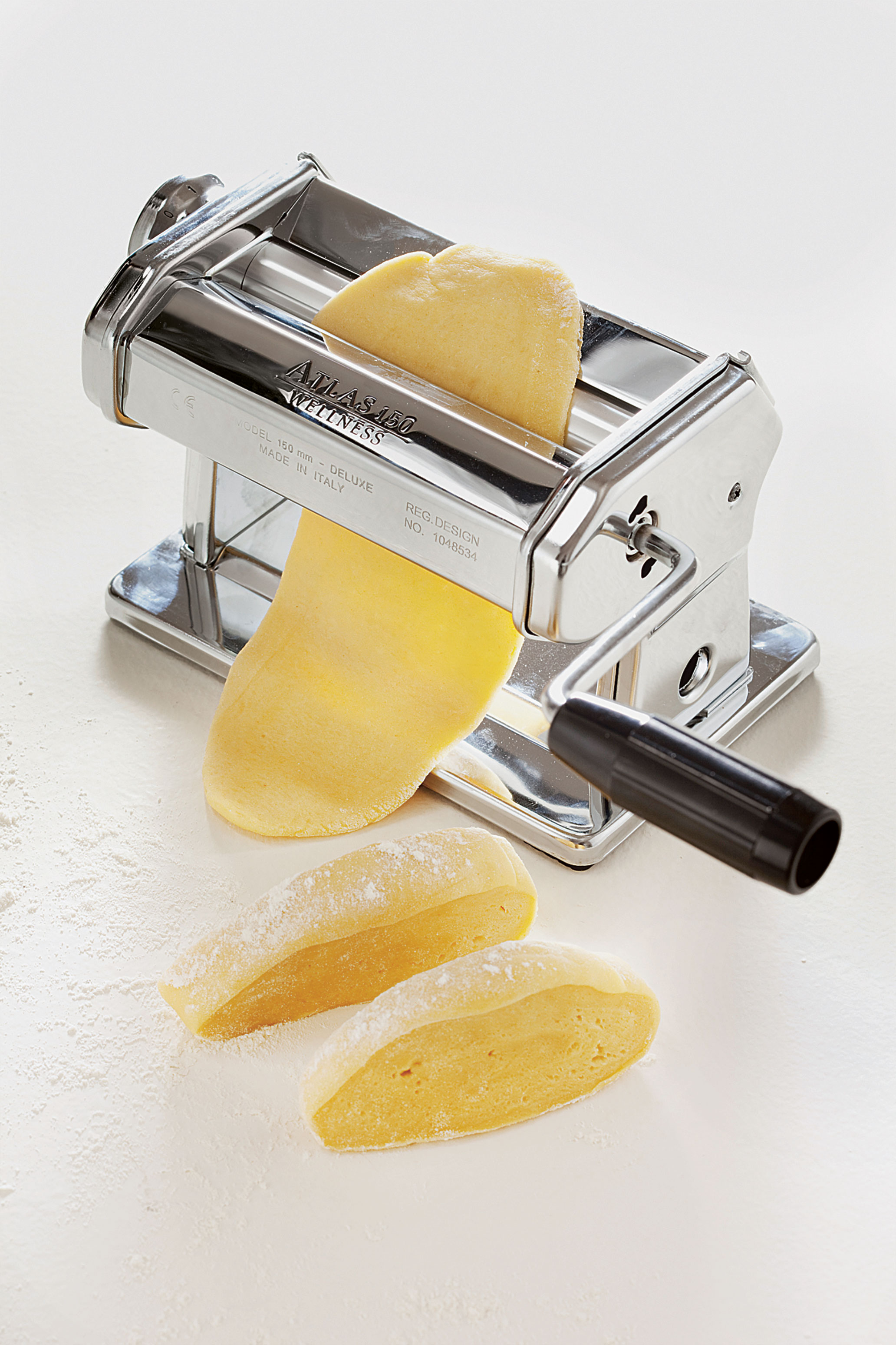 Fresh egg pasta being made in a pasta machine, as featured in The Silver Spoon Classic