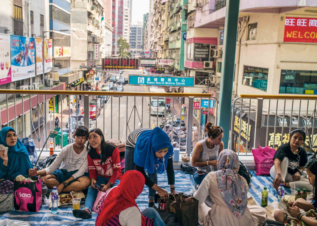 Hong Kong. As cities become denser, more complex and more contested, open space between buildings takes on special social significance. On Sundays, foreign domestic workers in Hong Kong congregate on sky-bridges and walkways to socialize outside the confines of their employers' homes, celebrating their cultural identity as 'interlocal' citizens