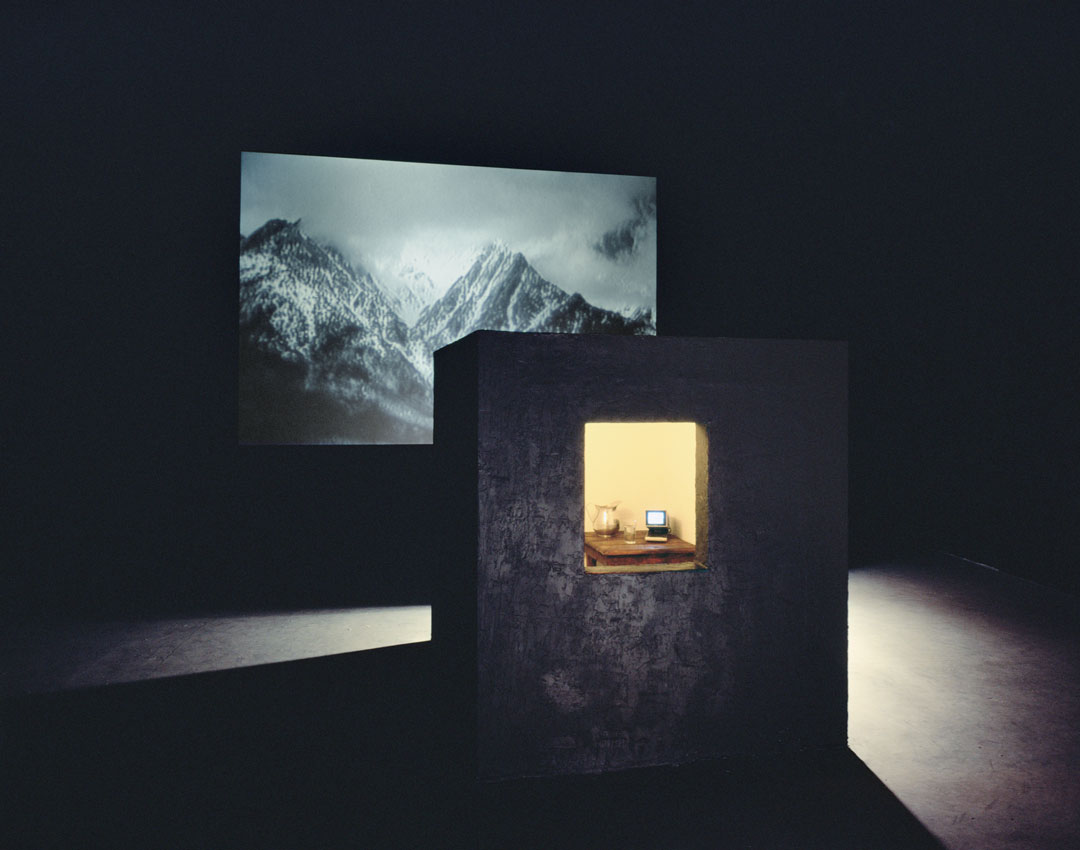 Bill Viola, Room for St. John of the Cross, 1983. Video and sound installation in a dark room, with a black cubicle with window, peat moss, wooden table, glass and metal pitcher with water, color video, and one-channel mono sound; black-and-white video projection; amplified stereo sound; room: 14 x 24 x 30 ft; projected image: 8 ft. 7 in. x 12 ft. 8 in; continuously running