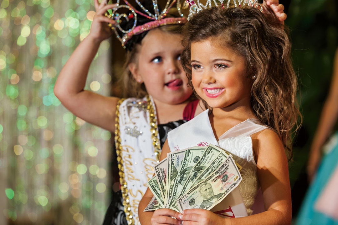 "Kailia Deliz, 5, receiving her cash award for winning the Ventura County ""Summer Fun"" Beauty Pageant, Oxnard, California, 2011. The following year Kailia won $10,000 at the Universal Royalty National Pageant, a competition that is featured on the TV show Toddlers and Tiaras. From Generation Wealth by Lauren Greenfield"