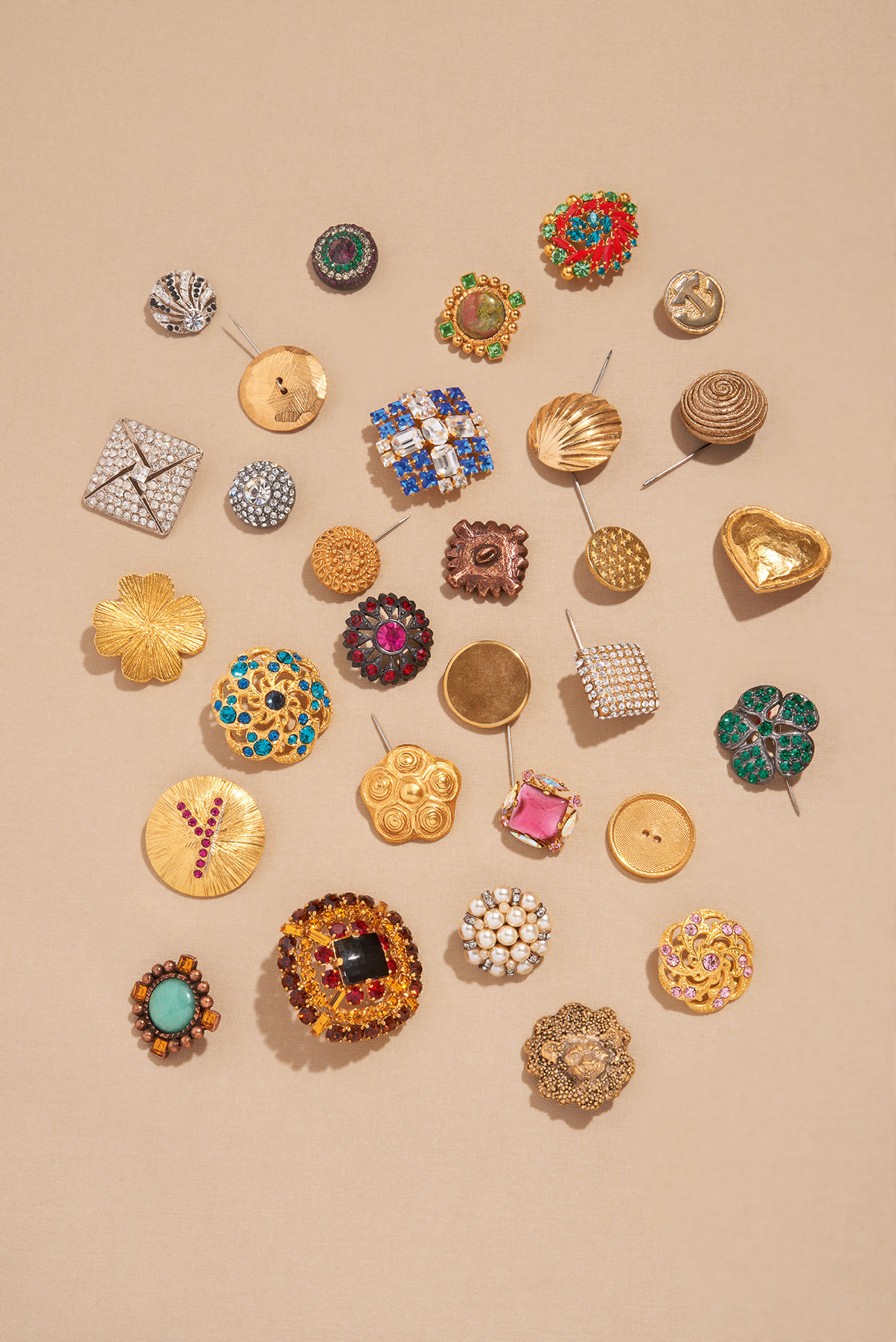 A selection of silvered and gilt metal, coloured diamanté and glass paste buttons from the trays of buttons in Yves Saint Laurent's studio