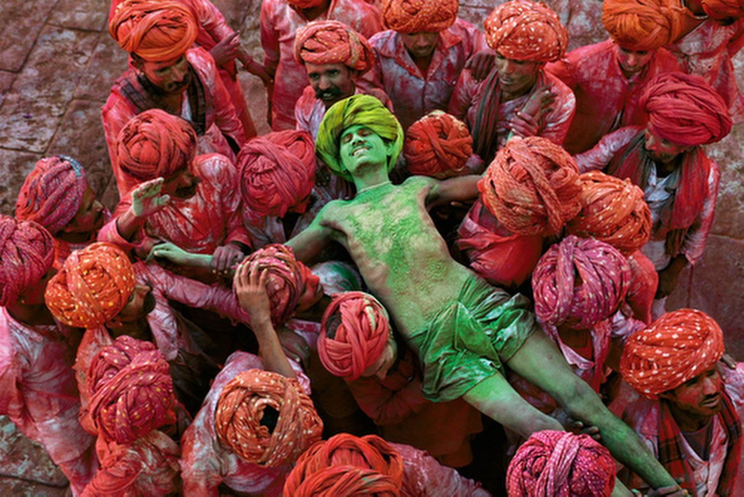 Rajasthan, 1996. A crowd carries a man during the Holi festival. Photograph by Steve McCurry