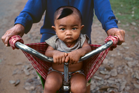 Steve McCurry, Baby in a bicycle sling at Banteay Srei, Angkor, Cambodia (2000)