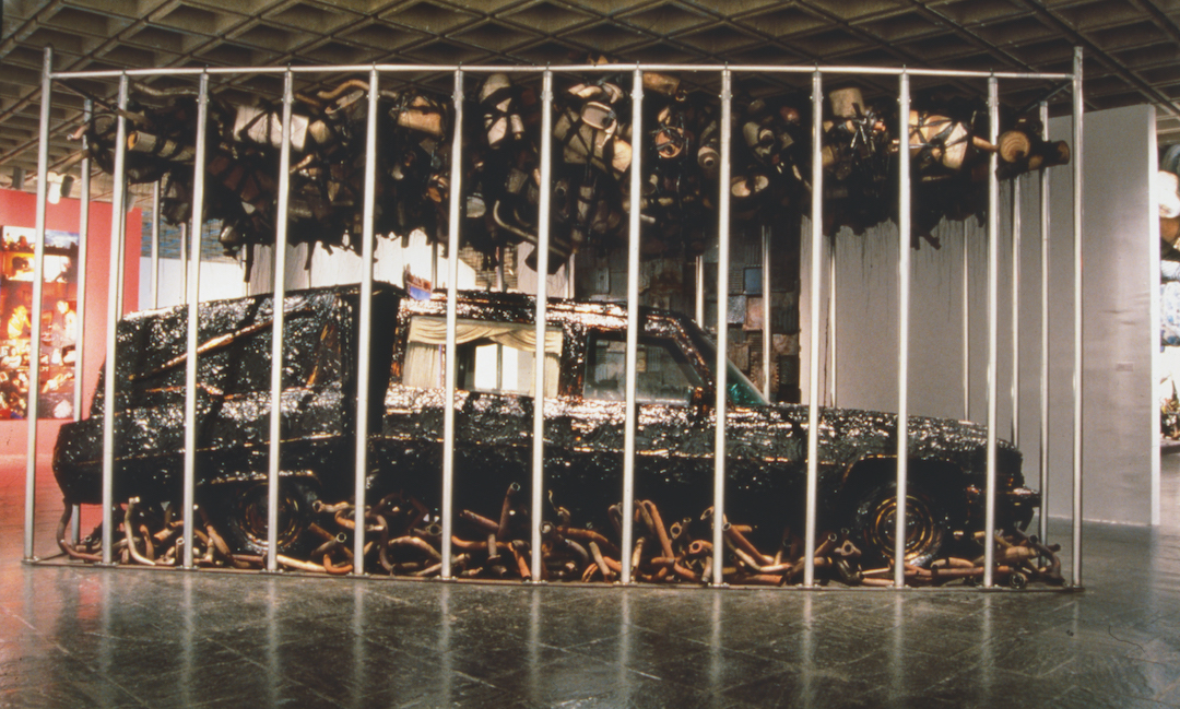 Nari Ward, Peace Keeper, 1995. Hearse, grease, mufflers, and feathers, 144 x 116 x 264 in (365.8 x 294.6 x 670.6 cm). Installation views: Whitney Museum of American Art, New York, 1995. Courtesy the artist, Lehmann Maupin, New York, Hong Kong, and Seoul, and Galleria Continua, San Gimignano, Beijing, Les Moulins, and Havana