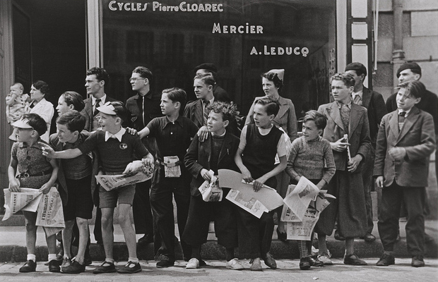 Robert Capa, 'Watching the Tour de France in front of the bicycle shop owned by Pierre Cloarec, one of the cyclists in the race, Pleyben, Brittany, France' (July, 1939)