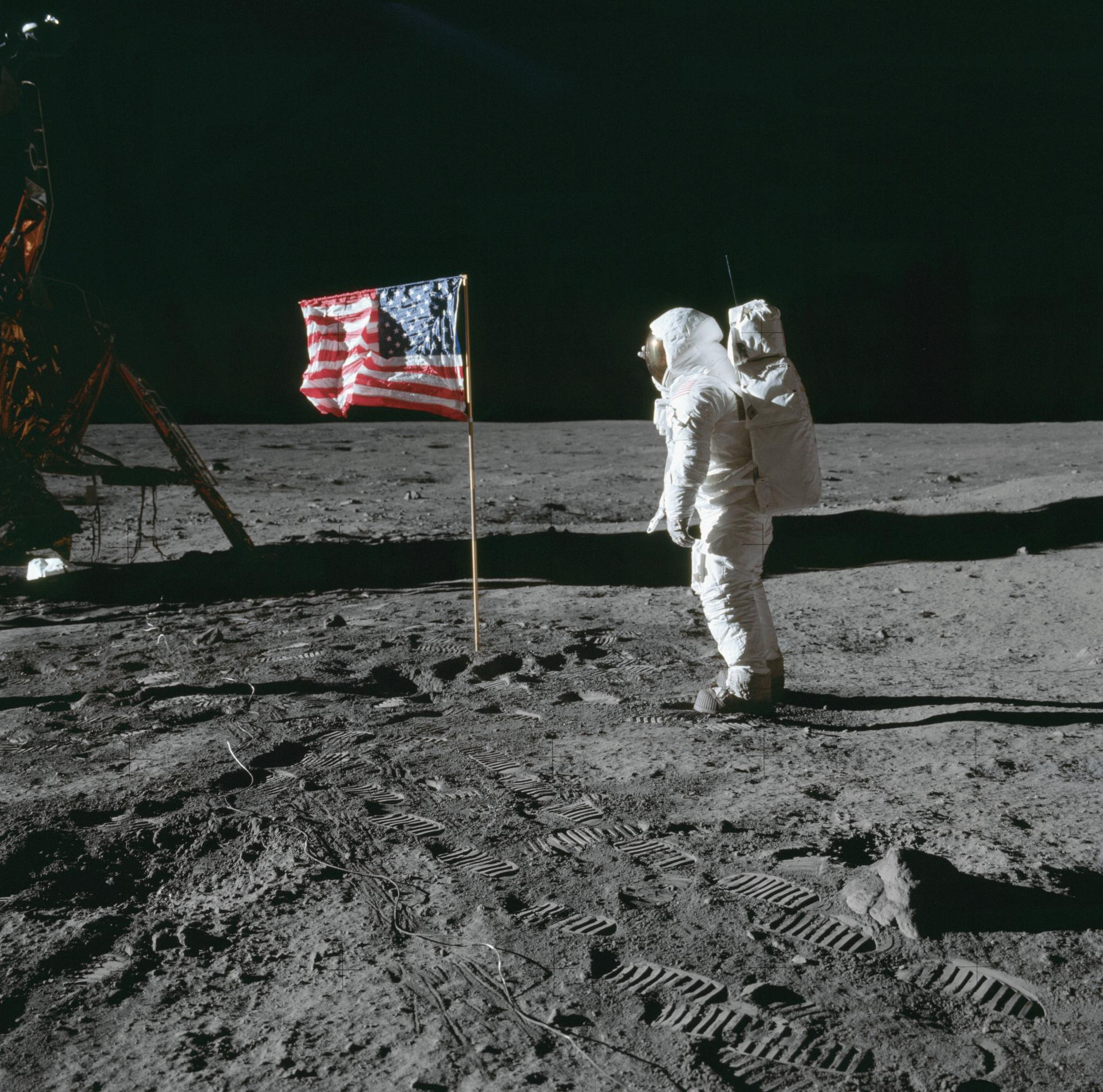 Astronaut Edwin E. Aldrin Jr., lunar module pilot of the first lunar landing mission, poses for a photograph beside the deployed United States flag during Apollo 11 extravehicular activity (EVA) on the lunar surface. Image courtesy of NASA