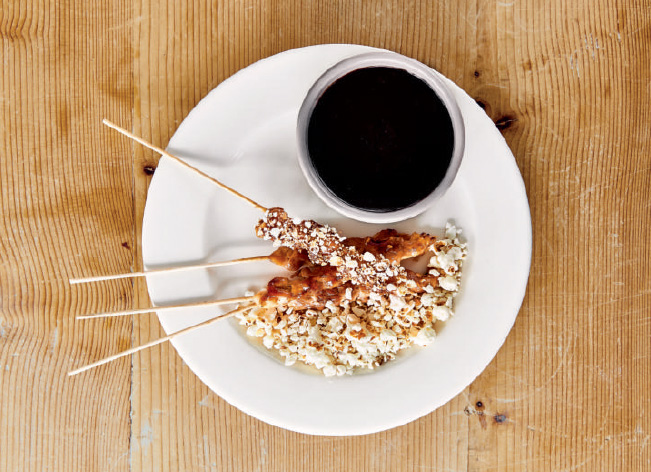 Chicken on sticks with soy sauce and popcorn, as reproduced in Bread is Gold