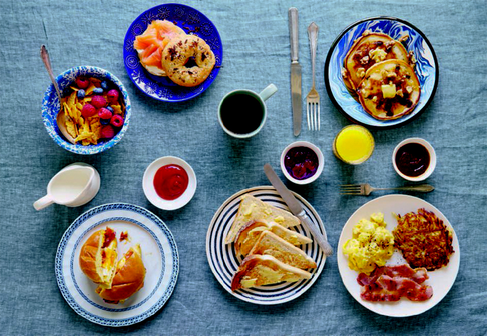 Clockwise from top left: toasted cornflakes; everything bagel with cream cheese and lox; pour-over coffee; orange juice; blueberry pancakes; the diner breakfast; diner toast; bacon, egg, and cheese sandwich, from the American breakfast pages of Breakfast: The Cookbook