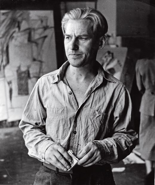 Willem de Kooning in his Fourth Avenue studio with drawings related to Woman I in the background, 1950; photograph by Rudy Burckhardt. Artwork by Willem de Kooning © 2014 The Willem de Kooning Foundation/Artists Rights Society, (ARS), New York
