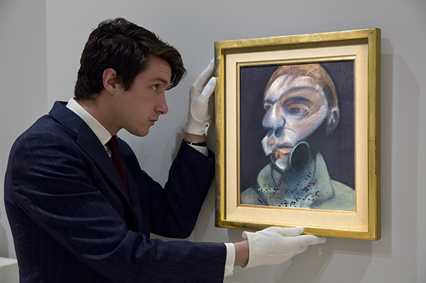 A Sotheby's employee with Francis Bacon, Self-Portrait, 1975,  oil on canvas, 35.5 by 30.5cm, est. £10-15 million. Image courtesy of Sotheby's
