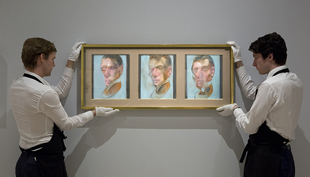Two Sotheby's employees with Francis Bacon, Three Studies for Self-Portrait, 1980, oil on canvas, each: 35.5 by 30.5cm est. £10-15 million. Image courtesy of Sotheby's