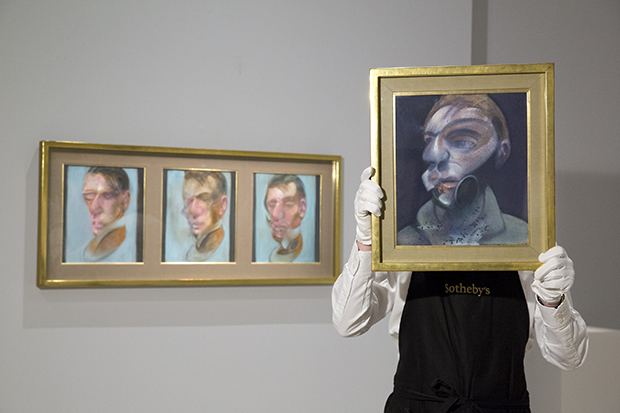 A Sotheby's employee holding Francis Bacon, Self-Portrait, 1975,  oil on canvas, 35.5 by 30.5cm, est. £10-15 million. Behind: Francis Bacon, Three Studies for Self-Portrait, 1980, oil on canvas, each: 35.5 by 30.5cm est. £10-15 million. Courtesy of Sotheby's