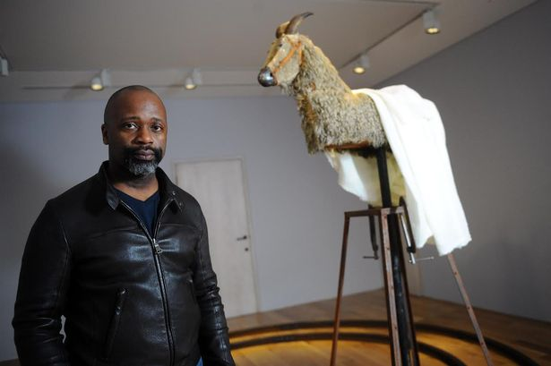Theaster Gates beside his work, A Complicated Relationship between Heaven and Earth, or When We Believe