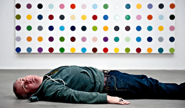 Damien Hirst in front of one of his spot paintings in 2011