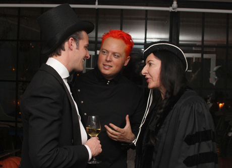 Marina Abramović (right) speaks to guests including Jamie Prentice (left) and John Kluge Jr. (middle) at her Halloween party on Monday night