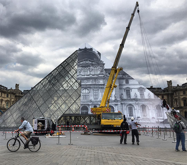 JR's work goes up on the Louvre Pyramid. Image courtesy of JR's Instagram