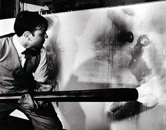 Yves Klein creating one of his fire action paintings, 1961