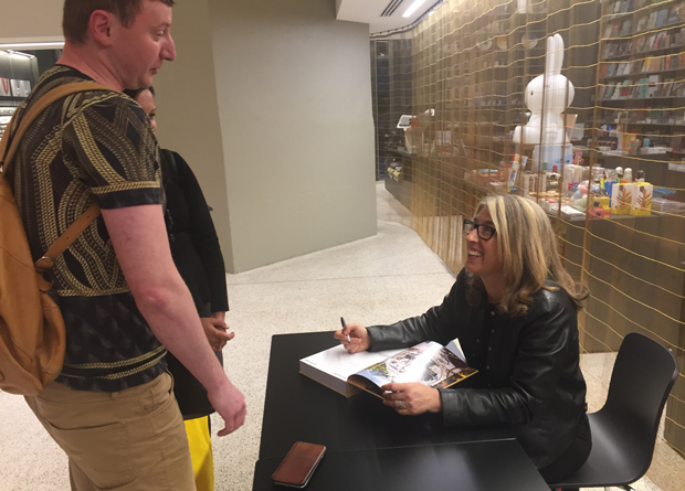 Lauren Greenfield signs a copy of Generation Wealth for a fan after her talk