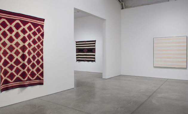 Who knows why these Agnes Martin paintings are hanging beside Navajo blankets?