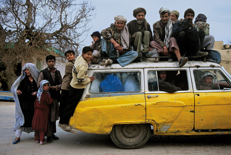 Steve McCurry, People sitting on and crowding inside a taxi, Mazar e sharif (2003)