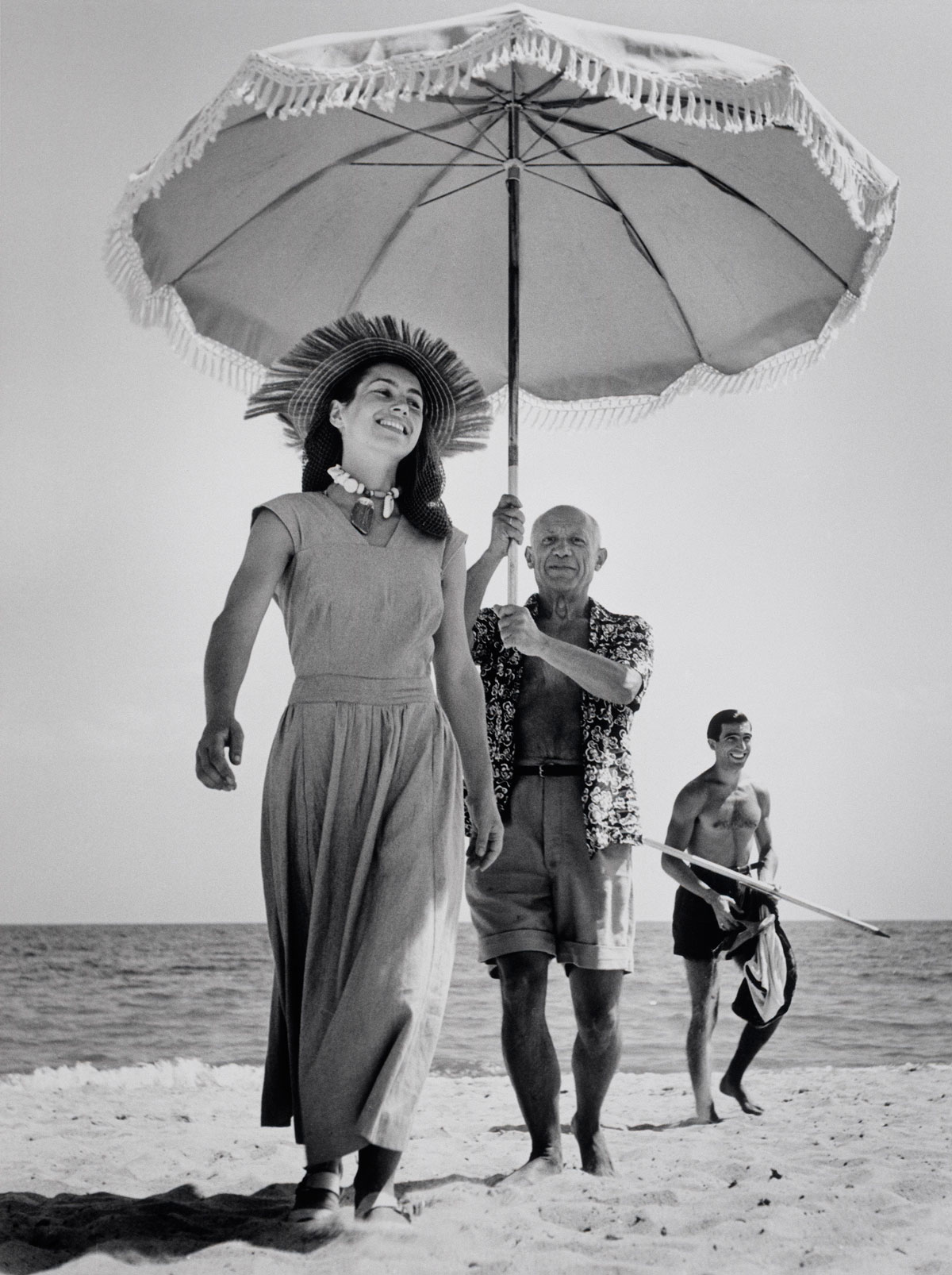 Pablo Picasso with his nephew Javier Vilato and Françoise Gilot on the beach. Golfe-Juan, France. August, 1948 © Robert Capa © International Center of Photography / Magnum Photos