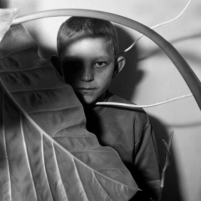 Study of Boy and Plant 1999 Outland 40x40 cm Gelatin silver print Copyright Roger Ballen