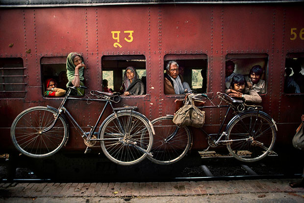Bicycles hang on the side of a train - Steve McCurry from the book India