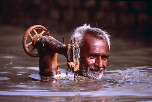 Porbandar, Gujarat 1983 - Tailor carries his sewing machine through monsoon floodwaters - Steve McCurry