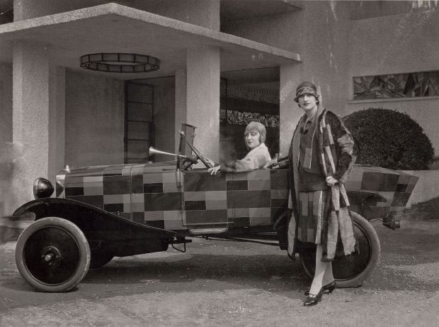 Two models wearing fur coats designed by Sonia Delaunay and manufactured by Heim, with the car belonging to the journalist Kaplan and painted after one of Sonia Delaunay's fabrics, in front of the Pavillon du Tourisme designed by Mallet-Stevens, International Exposition of Modern Industrial and Decorative Arts, Paris 1925. Bibliothèque nationale de France