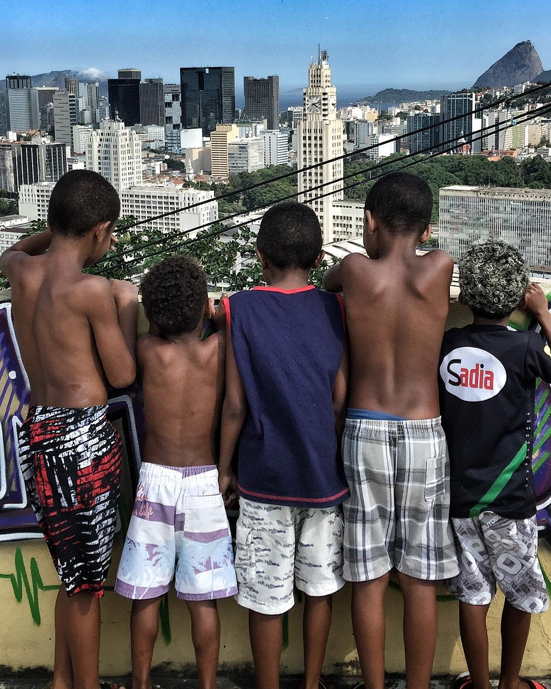 Local kids look down from the roof terrace at Casa Amarela. Image courtesy of JR's Instagram